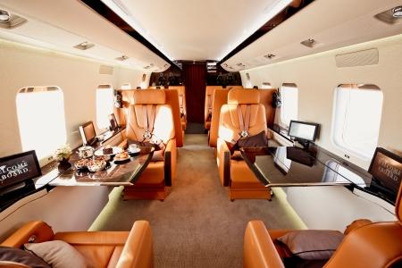Prive vliegtuig interieur met houten tafels en lederen zetels