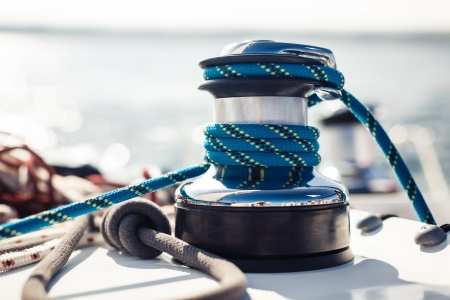 rigging: Closeup on yacht cord crank, rope holder on white sail  Stock Photo