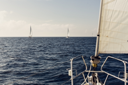Sailing ship yachts with white sails in the open sea photo