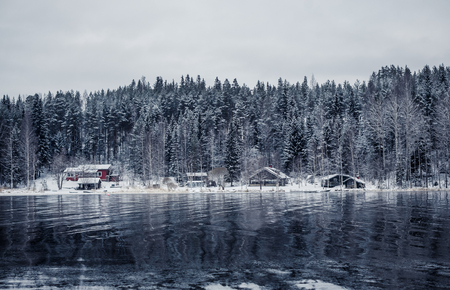 Wooden cottage by the river in winter forest covered by snow in Central Finland photo