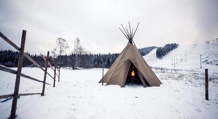 norte: Wigwam con fuego en el bosque de invierno, Finlandia Central