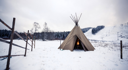 Wigwam with fire in winter forest, Central Finland