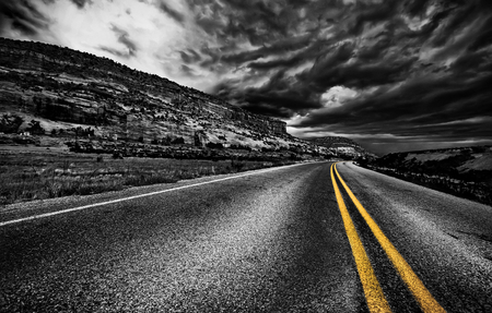 Road in the field with dramatic gray sky, USA