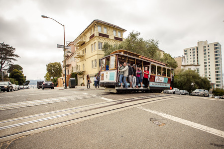 SAN FRANCISCO - JULY 26: Passengers enjoy a ride in a cable car on July 26, 2012 in San Francisco. It is the oldest mechanical public transport in San Francisco which is in service since 1873.