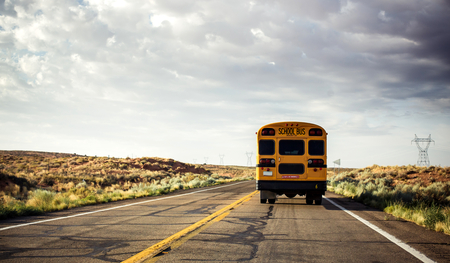 Yellow school bus on the road, USA