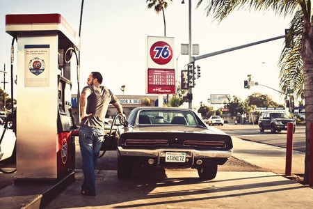 benzine: CALIFORNIA, USA - AUGUST 5, 2012: Man filling the car with gasoline in gas stations on August 5, 2012, San Diego, CA, USA Editorial