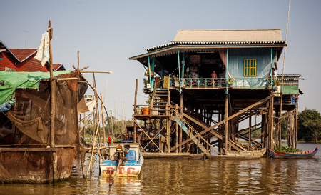 stilts: TONLE SAP, CAMBODIA - JANUARY 01: Unidentified people ride a boat in floating village on Tonle Sap lake on 01.2014 January. It is the largest lake in Southeast Asia (up to 16,000 square km). Editorial