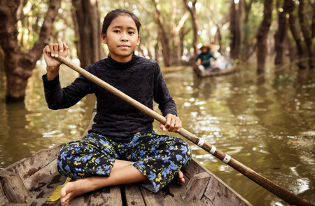 KAMPONG PHLUK,CAMBODIA - JANUARY 01: Unidentified Cambodian woman rowing her boat in Tonle Sap water village on 01.2014 January, Siam Reap,Cambodia