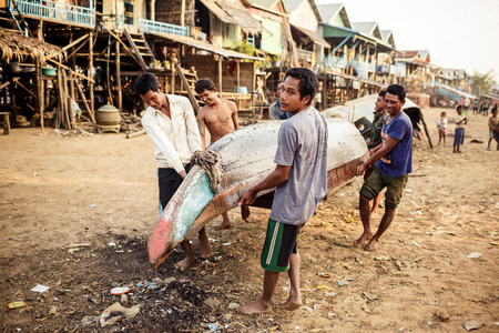 sap: TONLE SAP, CAMBODIA - JANUARY: Unidentified khmer people repair their bot on Tonle Sap lakeo on 01.2014 January. It is the largest lake in Southeast Asia (up to 16,000 square km). Editorial