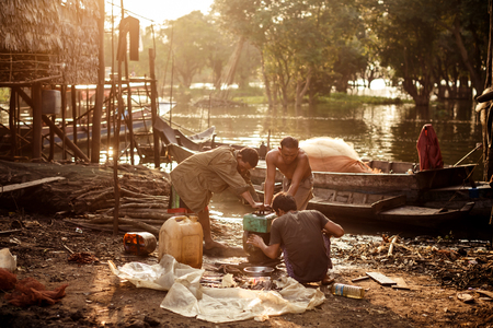 TONLE SAP, CAMBODIA - JANUARY: Unidentified khmer people repair their bot on Tonle Sap lakeo on 01.2014 January. It is the largest lake in Southeast Asia (up to 16,000 square km).