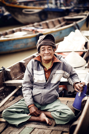 Old man on a boat in river, Vietnam.
