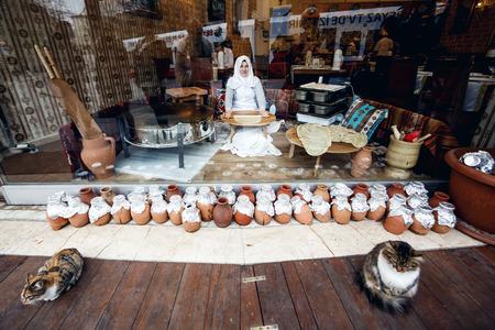 saleslady: ISTANBUL, TURKEY - NOVEMBER 29: Woman sitting in showcase and making pitas for sale, Istanbul, Turkey on November 29, 2014