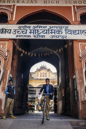 maharaja: JAIPUR, INDIA - JANUARY 10, 2015: School student boy on bicycle near Maharaja High School on January 10, 2015 in Jaipur, India