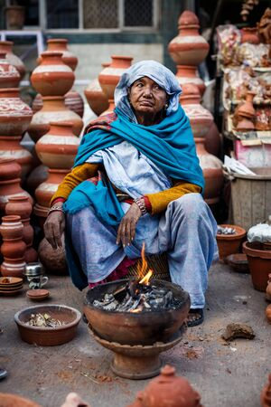 ollas de barro: DELHI, INDIA - 4 de enero de 2015: Mujer india que vende ollas de barro en el mercado local el 4 de enero, 2015, en Nueva Delhi, India