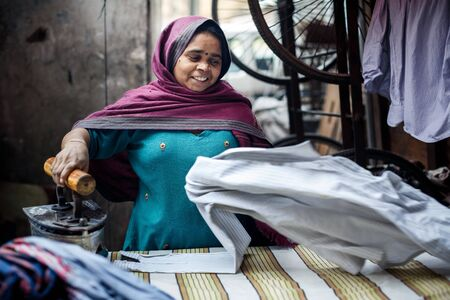 working woman: DELHI, INDIA - JANUARY 4, 2015: Mature Indian woman ironing clothes on January 4, 2015 in Delhi, India