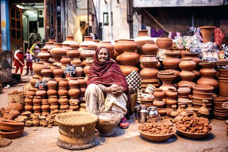 ollas de barro: DELHI, INDIA - 4 de enero de 2015: Mujer india que vende ollas de barro en el mercado local el 4 de enero, 2015, en Nueva Delhi, India