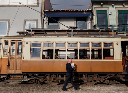 trams: PORTO, PORTUGAL - OCTOBER 19, 2015: Driver of Famous old tram on street of Porto. Trams operating in Porto since 1872 Editorial
