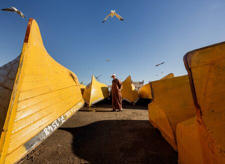 yellow boats: ESSAOUIRA, MOROCCO - NOVEMBER 4, 2015: Unidentified fisherman in front of yellow boats in the port on the coast of Essouira, Morocco.