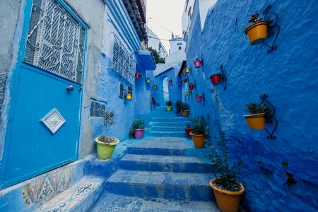Sun flower: Eine der Straßen in Chefchaouen in Marokko. Alle Häuser und Wände sind blau lackiert. Beliebtes Touristenziel in Marokko. Lizenzfreie Bilder