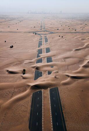 Empty road in desert covered by sand, Dubai, UAE
