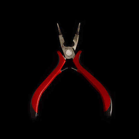 Used pliers on a black background isolate
