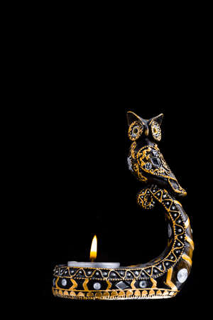 Candlestick owl with candles on a black background isolate
