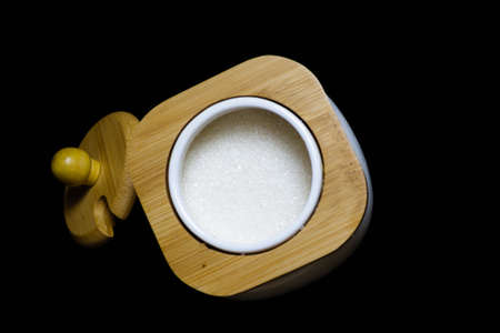 Sugar bowl with bamboo lid on a black background