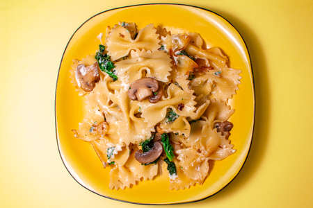 butterfly pasta with fried mushrooms, green spinach on a yellow plate on an orange background