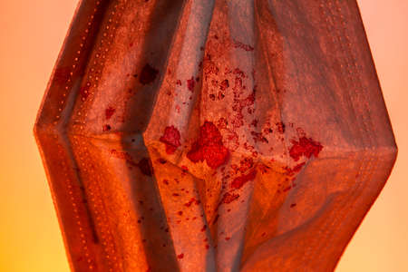 Medical gauze mask in dried blood on an orange background. close up copy space Stock Photo