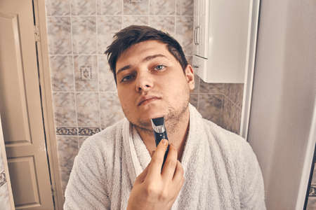 guy in a white coat shaves with a trimmer in the bathroom. close up Banco de Imagens