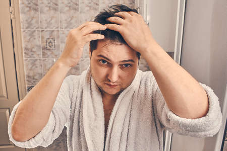 a man in a white dressing gown straightens his hair on his head in the bathroom. Banco de Imagens