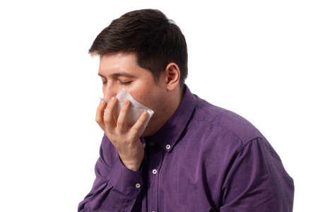Fat man in a purple shirt vomits in a napkin on a white background. isolate. copy space