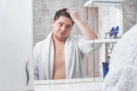 a man in a white bathrobe straightens his hair on his head through a mirror in the bathroom. Banco de Imagens