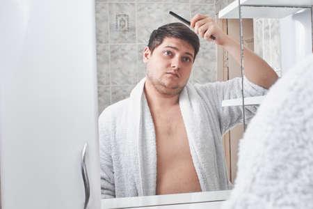 a man in a white bathrobe straightens a comb hair on his head through a mirror in the bathroom. Banco de Imagens