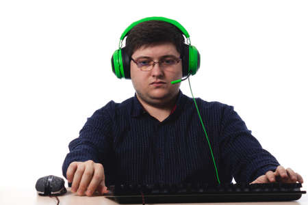 Young guy in a dark blue shirt green headphones gamer in glasses for vision on a white background. isolate. copy space