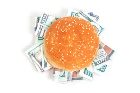 burger with hundred dollar bills instead of toppings on a white background isolate top view