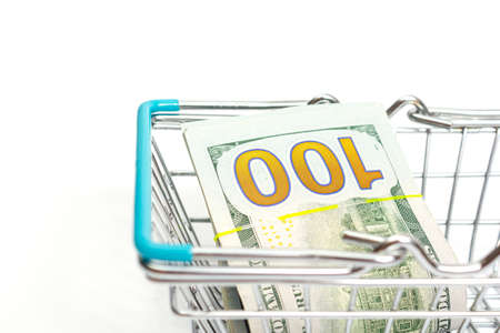 a basket with blue inserts is inserted into a bundle of hundred-dollar bills lies on a white background. isolate