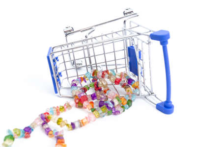 fallen shopping cart with beads of multi-colored gemstones on a white background. isolate