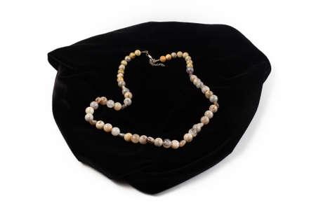 beads from natural Jasper river on black velvet. On a white background isolate