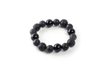 black shungite bracelet with solidified lava on a white background isolate Foto de archivo