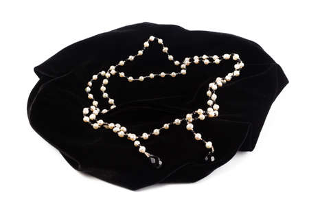 beads from natural River pearls on black velvet. On a white background isolate