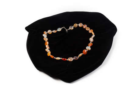 beads from natural Carnelian river on black velvet. On a white background isolate