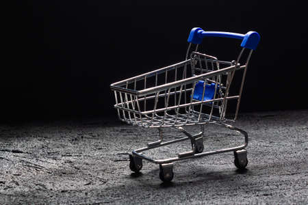 shopping cart with blue handle on black concrete dark background. copy space
