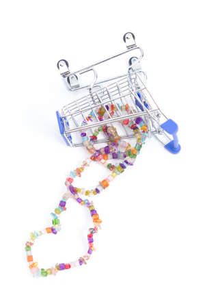 fallen shopping cart with beads of multi-colored gemstones on a white background. isolate, top view