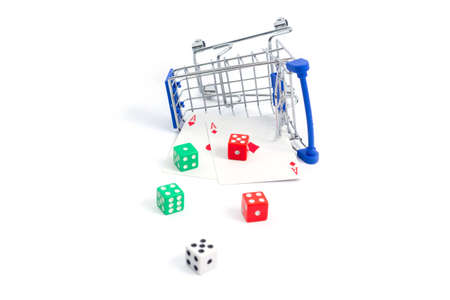 fallen shopping cart with playing cards two red aces diamond, heart and dice on a white background. isolate
