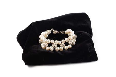 bracelet made of natural River pearls on black velvet. On a white background isolate Imagens