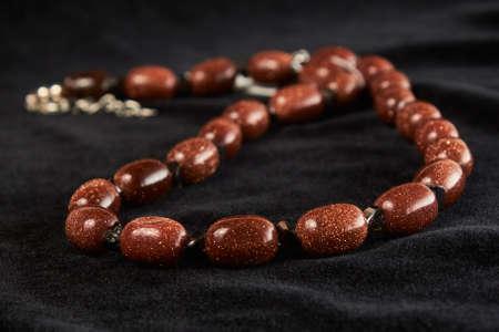 aventurine beads golden sands semiprecious stone on black velor. close up