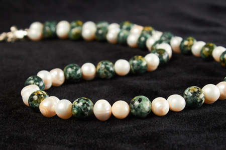 beads from pearls semiprecious stone on black velor. close up