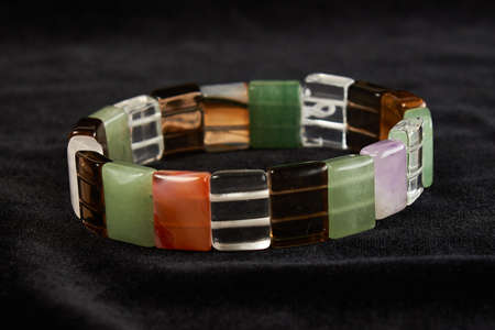 bracelet from different semiprecious stones on black velor. close up