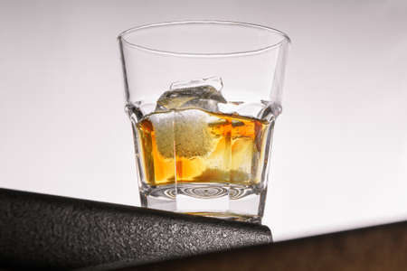 a glass of whiskey with ice stands on the corner of the bar in the center of the frame on a light gray background. close up, bot view. horizontal orientation Banco de Imagens